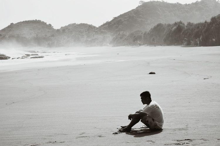 Full length of young man relaxing at balekambang beach during sunny day