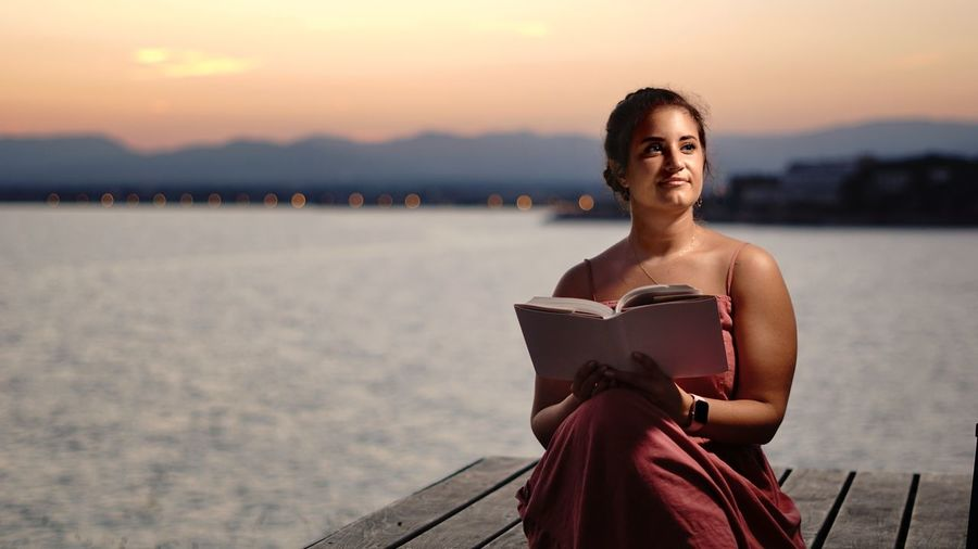 Portrait of smiling woman sitting against sky during sunset