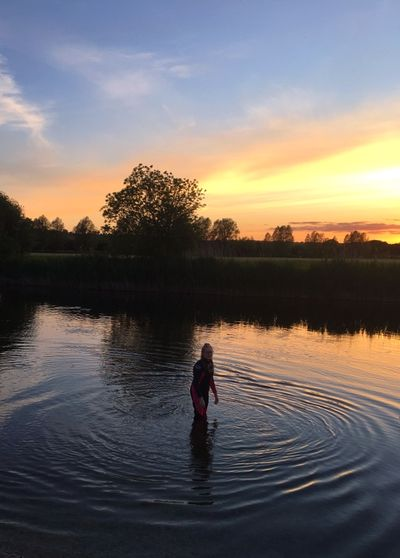 Person in lake against sky during sunset