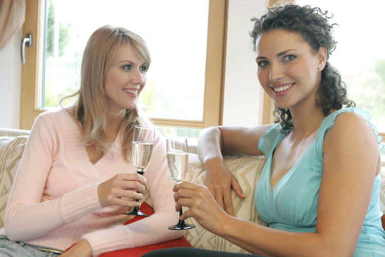 Portrait Of Cheerful Friends Drinking Champagne While Sitting At Home