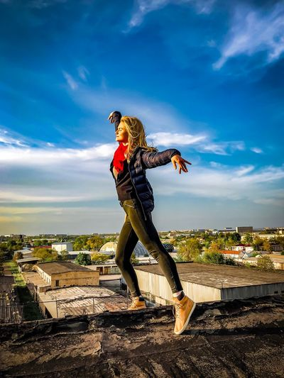 Woman dancing on building terrace against sky in city