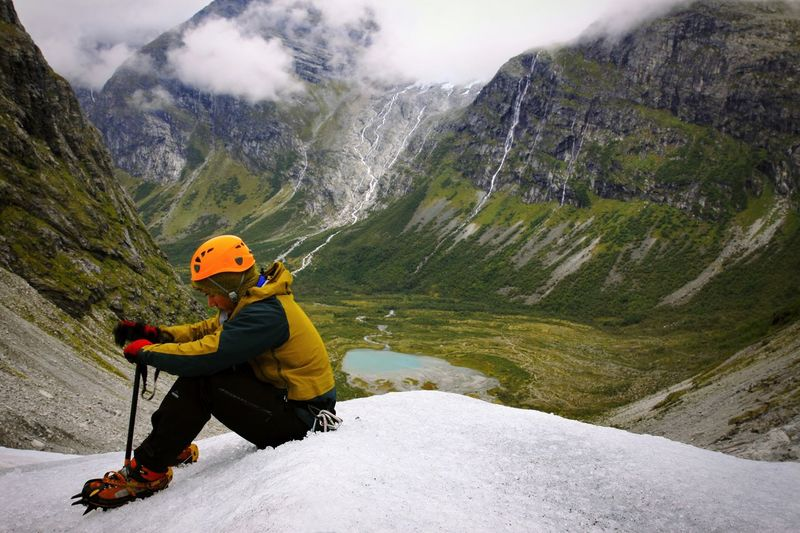 Full length of hiker sitting on glacier against rocky mountains