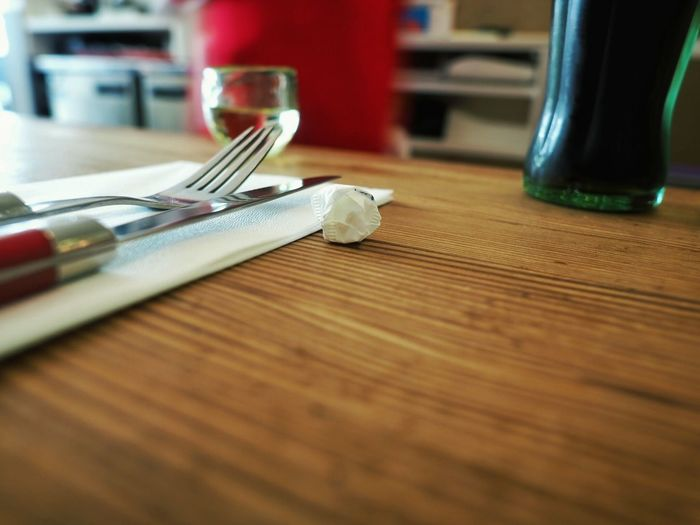 Close-up of crumpled paper by fork and knife on wooden table