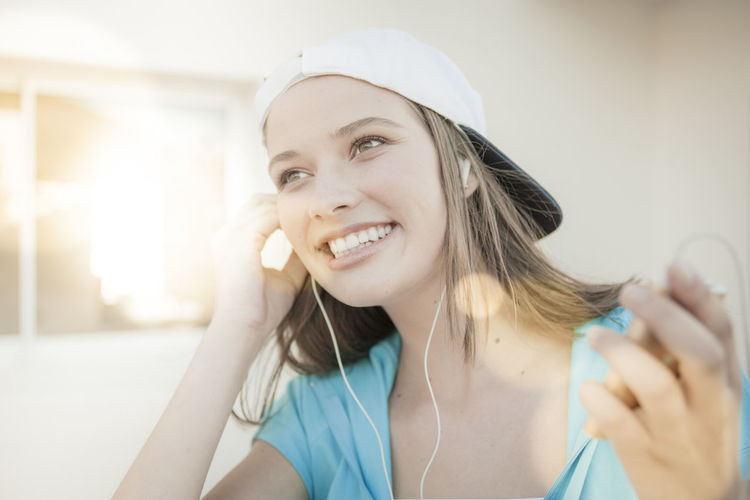 Portrait Of Smiling Young Woman Listening To Music