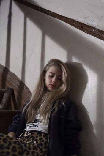 Portrait of young woman against wall