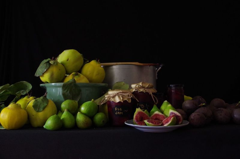 Fruits and vegetables on table against black background