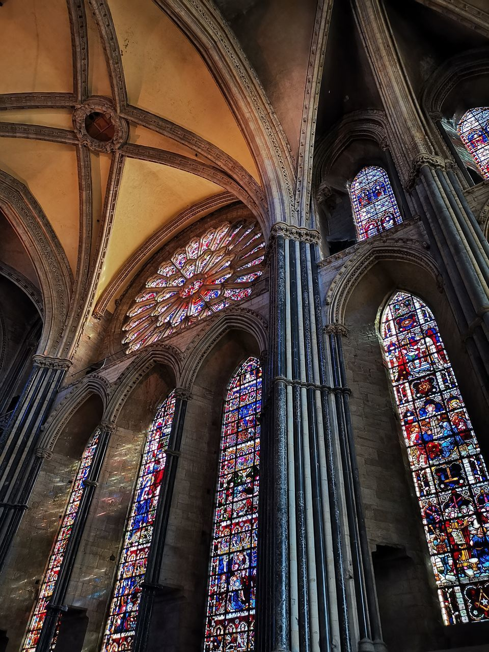 architecture, built structure, low angle view, place of worship, religion, spirituality, building, belief, arch, stained glass, indoors, architectural column, no people, glass, window, ceiling, architecture and art, abbey, gothic style