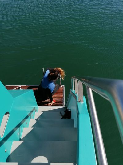 High angle view of woman sitting by ladder of boat on sea