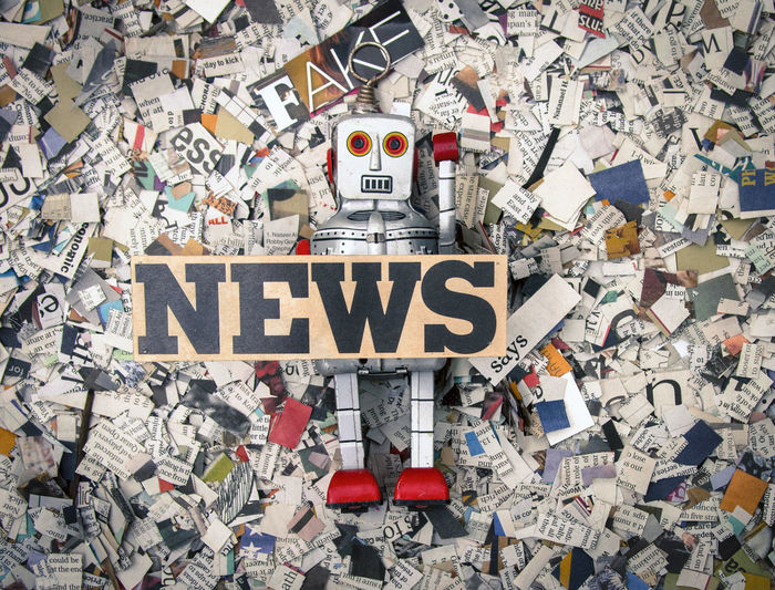 Directly above shot of robot with news text on newspapers