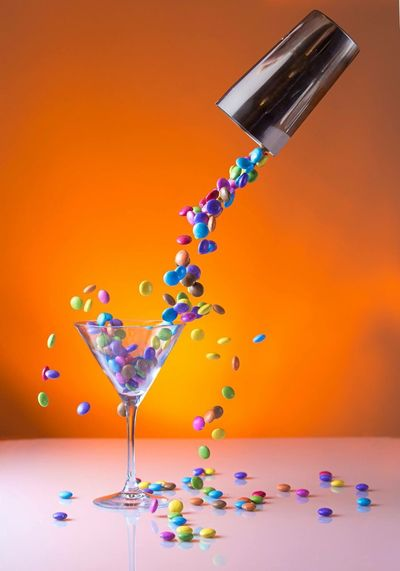 Gems candies falling from container in martini glass on table against orange background