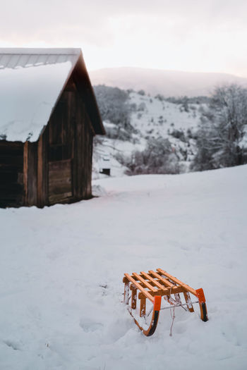 Snow on field against clear sky with wood sledge in front of a cabin during winter