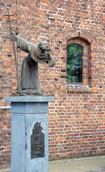 Statue against brick wall