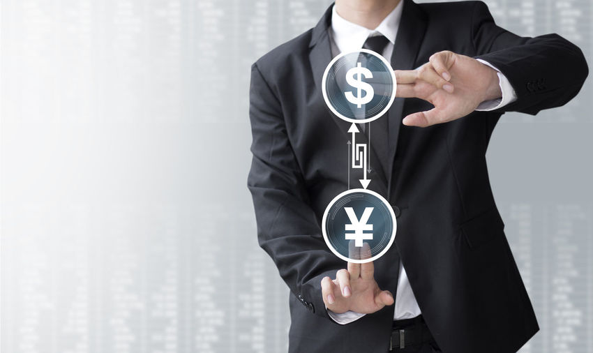 Digital Composite Image Of Man Touching Dollar And Yen Against White Background