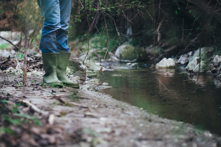 Body Part Casual Clothing Day Flowing Water Forest Human Body Part Human Leg Jeans Land Low Section Men Nature One Person Outdoors Plant Real People River Selective Focus Standing Stream - Flowing Water Tree Water
