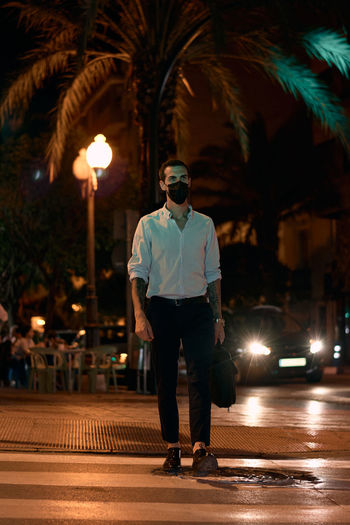 Full length of man standing on illuminated street at night