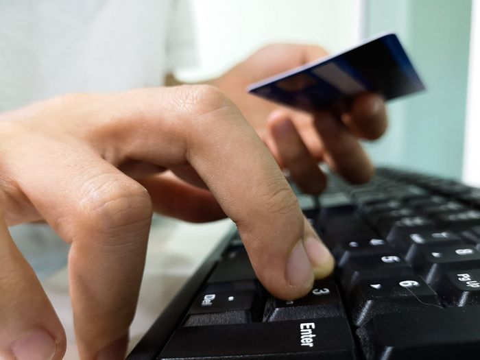 Close-up of person using computer while holding credit card