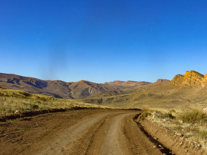 Dirt road leading towards mountains against clear blue sky