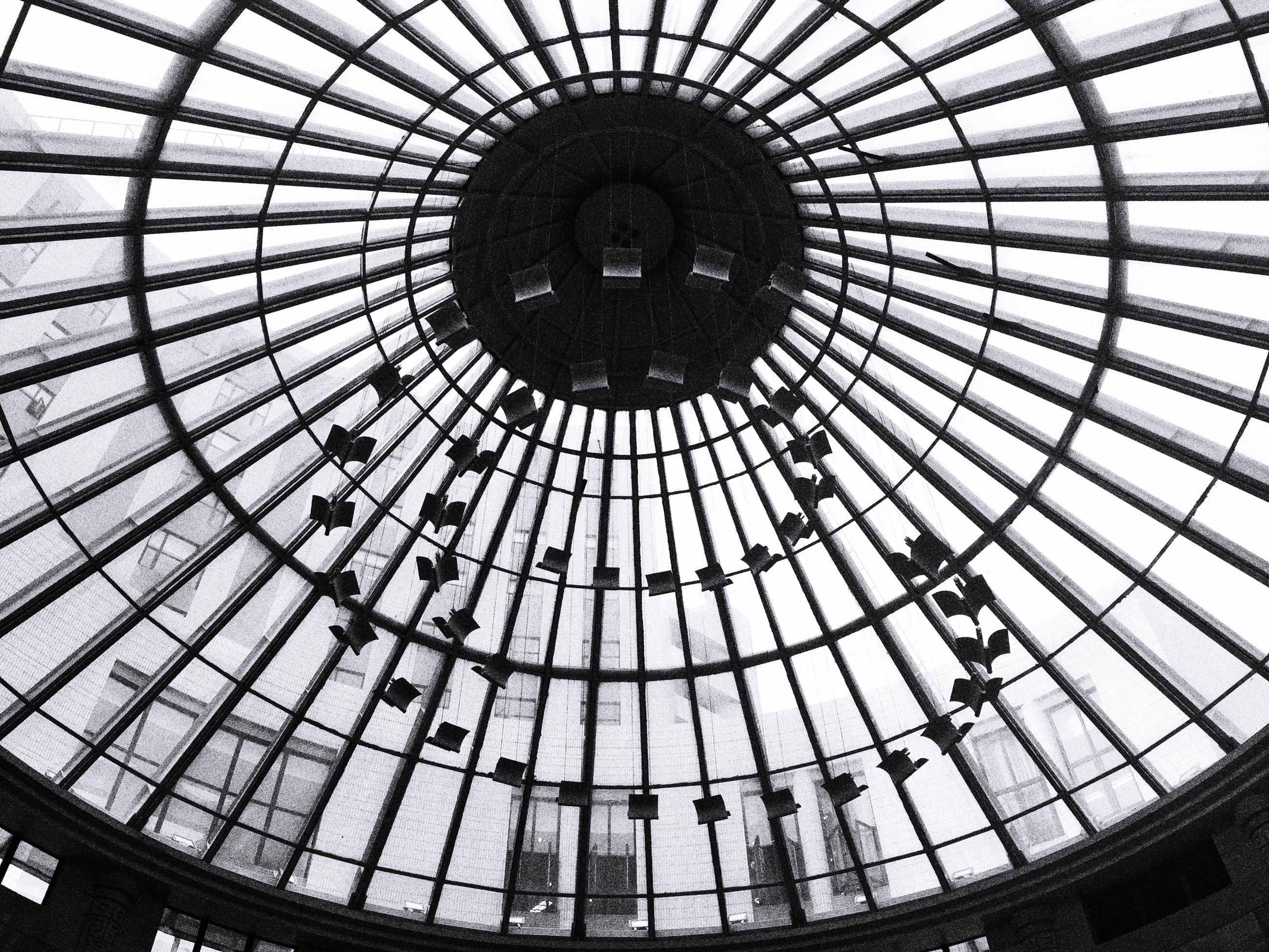 indoors, ceiling, architecture, low angle view, built structure, skylight, glass - material, pattern, architectural feature, directly below, circle, modern, dome, geometric shape, interior, transparent, design, famous place, shopping mall, travel