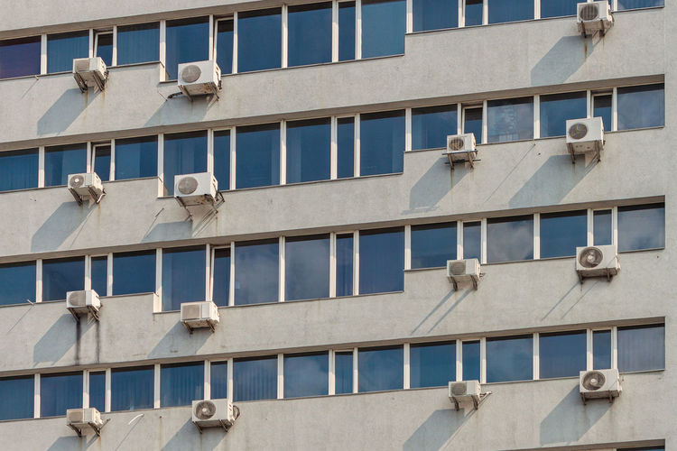 Lots of air conditioners on the wall of the building