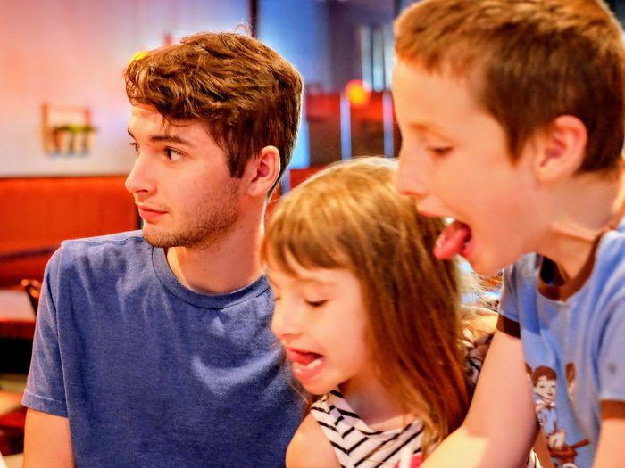 Playful siblings at restaurant