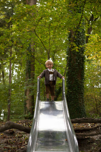 Green Innocent Laughing Traditional Clothing Trees Wood Blond Hair Boy Child Childhood Memories Forest Kid Lederhose Nature Outdoors Playing Playing Outside Slide Tree