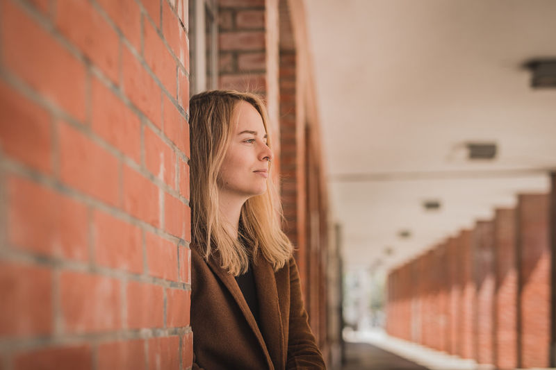 Young woman looking away while standing by brick wall