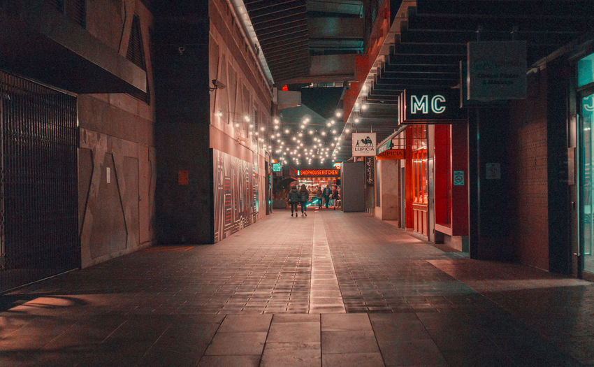 Arcade Architectural Column Architecture Building Building Exterior Built Structure Ceiling City Communication Diminishing Perspective Direction Empty Flooring Footpath Illuminated Incidental People Light Lighting Equipment Night Sign Text The Way Forward Tiled Floor