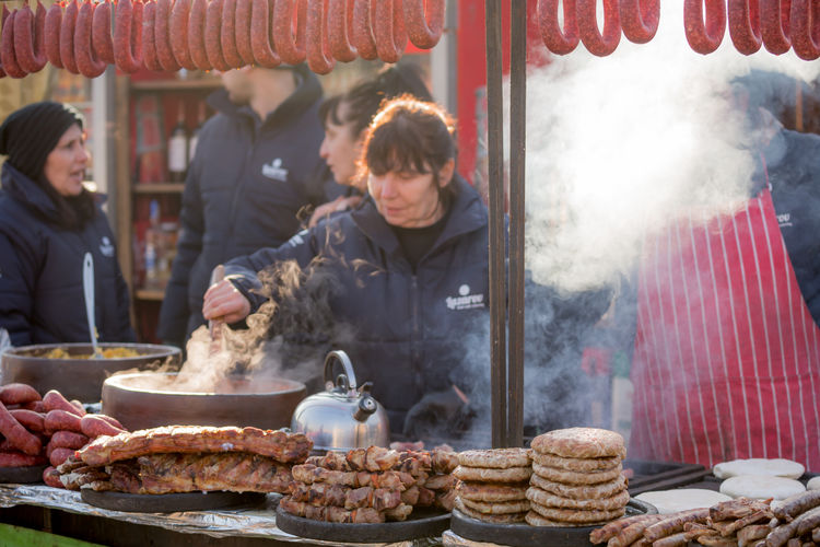 PERNIK, BULGARIA - JANUARY 26, 2018: Variety of delicious pork meals, kebab, sausages are being sold outdoors in the sunny winter day at the annual International Festival of Masquerade Games Surva Event Games Kukeri Kukeri, Bulgaria Adult Burning Day Festival Focus On Foreground Food Food And Drink Freshness Heat - Temperature Masquerade Men Occupation One Person Outdoors People Real People Retail  Small Business Smoke - Physical Structure Steam Surva Working Young Adult