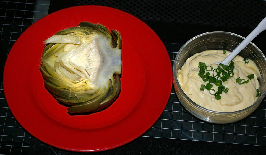 Homemade dish with half a boiled artichoke and a bowl of garlic mayonnaise aside Food And Drink Food Freshness Bowl Indoors  Healthy Eating Wellbeing Ready-to-eat Directly Above Still Life No People Close-up Table Vegetable High Angle View Red Kitchen Utensil Meal Serving Size Temptation Artichoke Garlic Mayonnaise