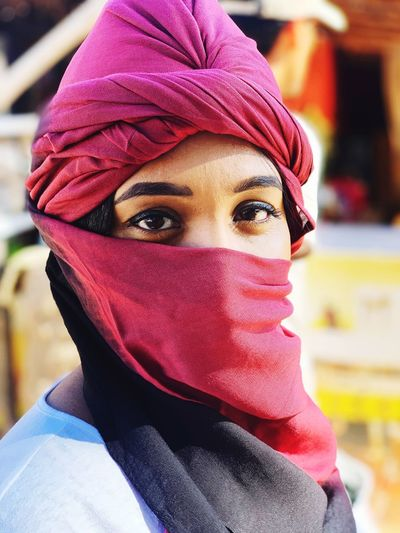Close-up portrait of woman face covered with scarf