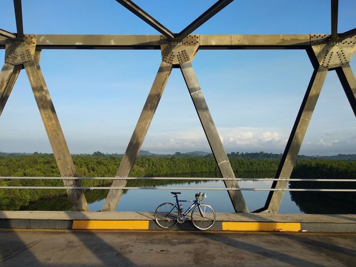 Bicycle on bridge against sky