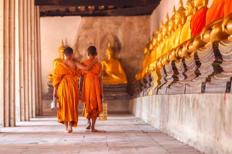 Rear view of novices walking in corridor of temple
