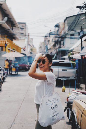 Side view of smiling woman standing in city