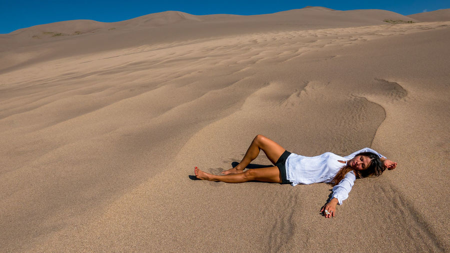 Full length of young woman lying on sand at desert