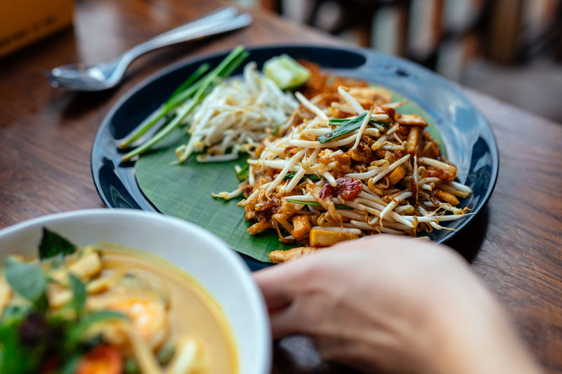 Cropped hand of person holding food in plate on table
