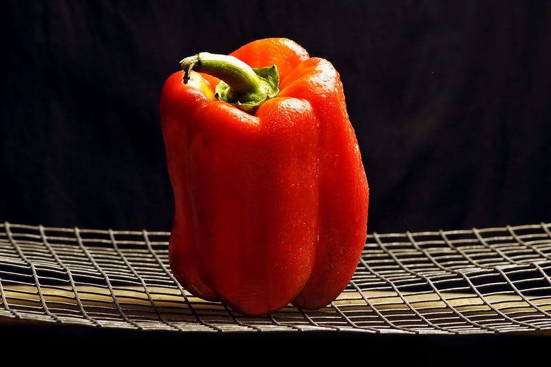 Close-up of red bell peppers against black background