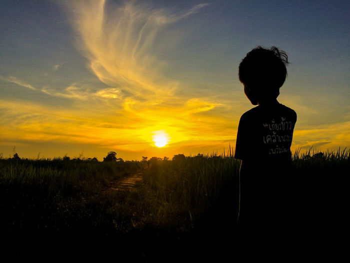 Rear view of silhouette man standing on field against sunset sky
