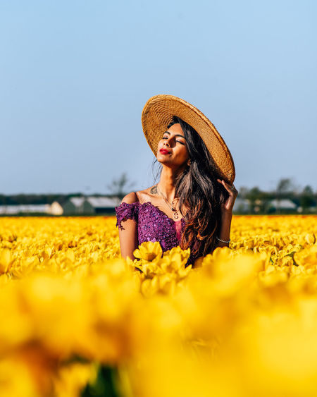 Woman wearing hat while standing by yellow flowering plants against clear sky