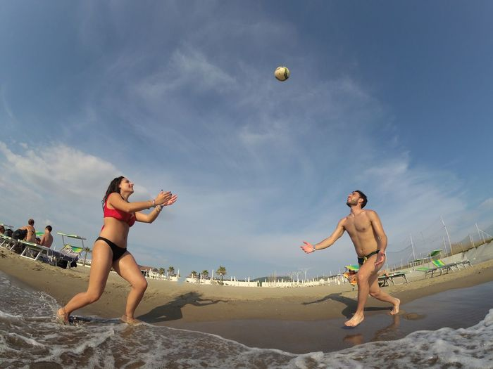 Low angle view of man and woman playing volleyball at beach against sky