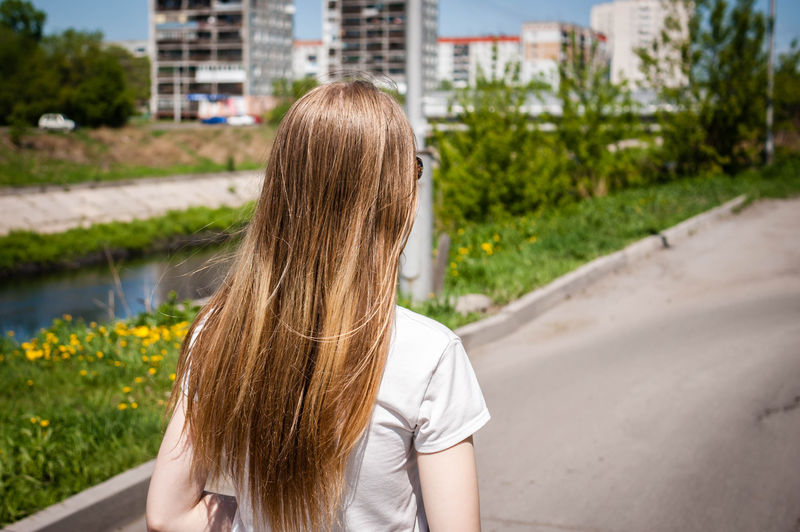Rear view of a teenage girl with blonde hair on street