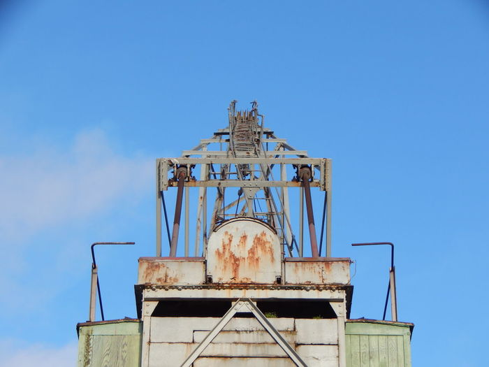 Low angle view of old rusty against blue sky