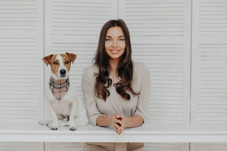 Portrait of smiling woman with dog sitting at table