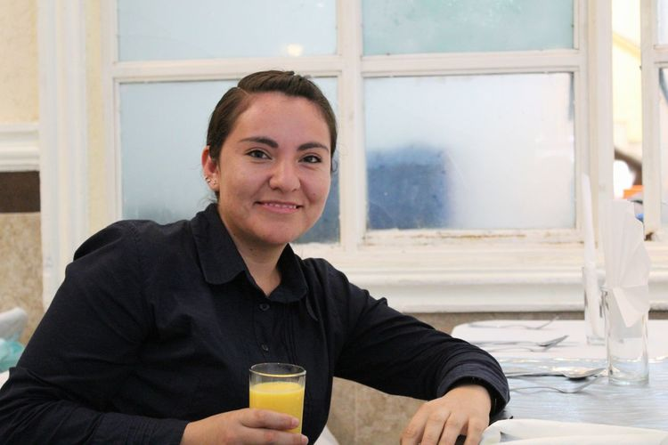Portrait of smiling mature woman with orange juice sitting at restaurant