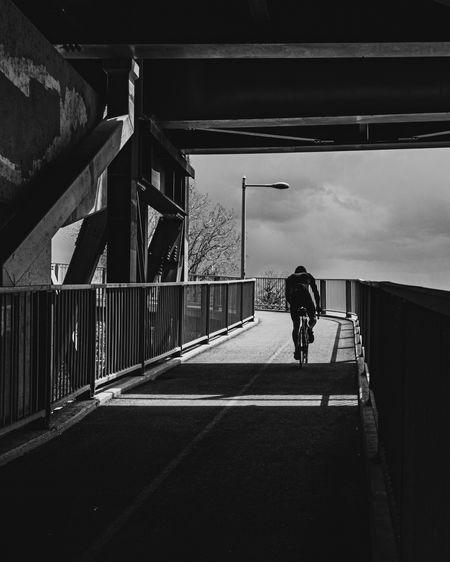 Rear view of man riding motorcycle on bridge