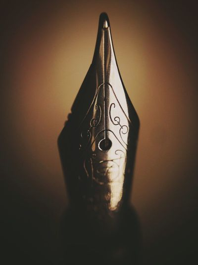 Close up of a fountain pen nib Writing Instrument Pen Fountain Pens Fountain Pen Nib Fountain Pen Pen Nibs Indoors  Shadow No People Wall - Building Feature Close-up Still Life Hanging Single Object Table Design Art And Craft Creativity Illuminated Vignette