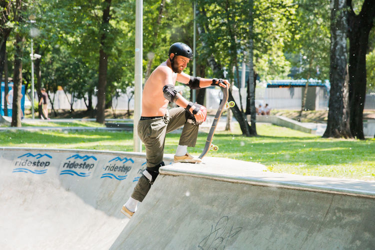 man skateboarding in a skatepark Tree Plant Sport Men Day Males  Leisure Activity Full Length People Holding Nature Two People Adult Determination Standing Weekend Activities Mid Adult Boys Helmet Outdoors Adolescence