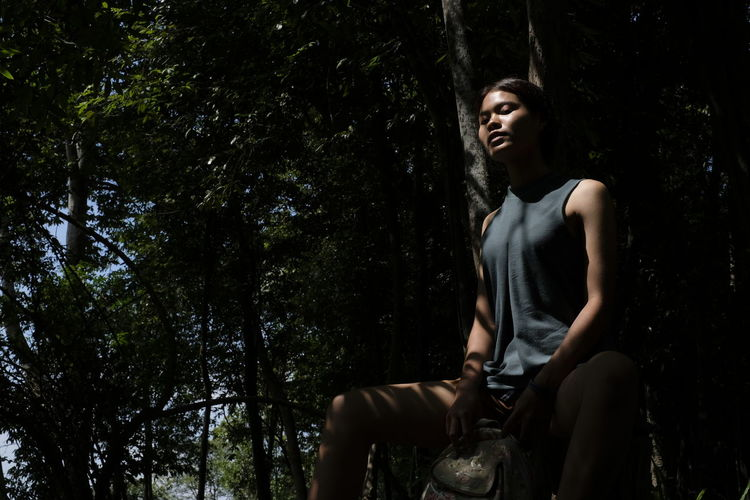 Thoughtful young woman sitting in forest