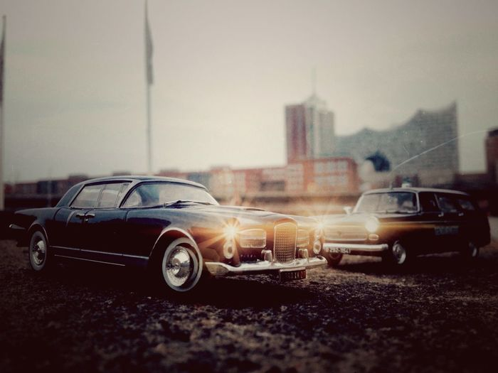 """Shot in Hamburg in front of the """"Elbphilarmonie"""" building. The cars are 8 cm long, miniature 1/43. in The front The beautiful Facel Vega and a Gendarmerie 404 Peugeot Break Car Transportation Land Vehicle Mode Of Transport Road No People Vehicle Outdoors Day Sky Police Car France Hamburg Architecture Movie EyeEmnewhear"""