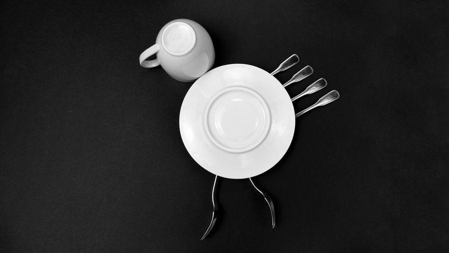 Directly above shot of upside down eating utensils on black background