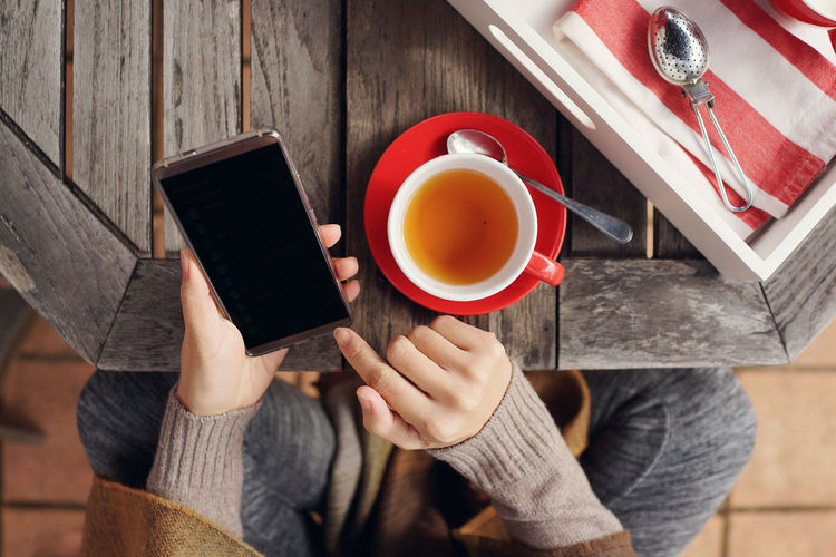 Female using smartphone and enjoying hot tea in garden Beverage Holding Hands Red Screen Winter Wooden Table Cold Days Cup Drink Flat Lay Food And Drink Garden Hand Holding Hot Drink Lifestyles Outdoors Smartphone Table Tea Cup Tea Time Technology Top View Using Phone Women